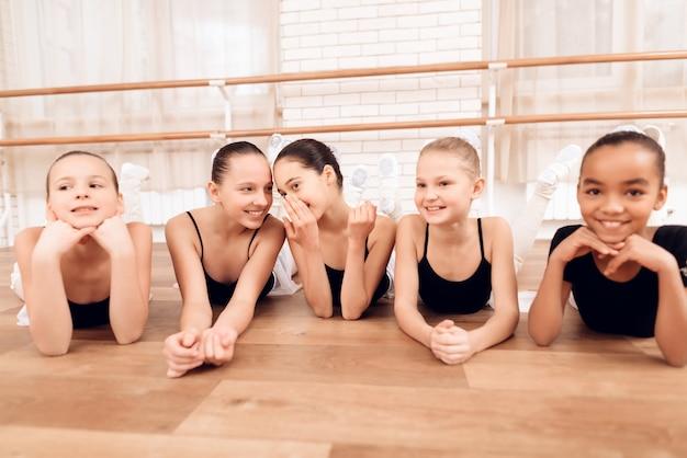 Junge ballerinas ruhen sich während einer pause im ballettunterricht aus.