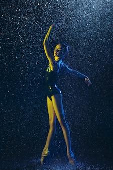 Junge ballettänzerin, die unter wassertropfen und -spray durchführt. kaukasisches modell tanzt in neonlichtern. attraktive frau. ballett und zeitgenössisches choreografiekonzept. kreatives kunstfoto.