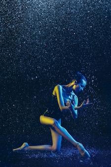 Junge balletttänzerin, die unter wassertropfen und -spray durchführt. kaukasisches modell, das in neonlichtern tanzt. attraktive frau. ballett und zeitgenössisches choreografiekonzept. kreatives kunstfoto.