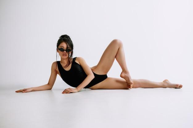 Junge balletttänzerin im schwarzen body gegen weiße studiowand