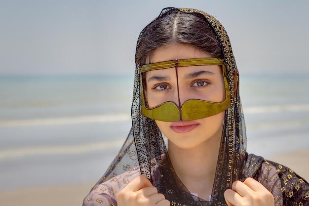 Junge bandarifrau, die traditionelle maske namens burka, küste des persischen golfs nahe stadt von bandar abbas, iran trägt.