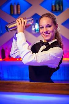 Junge bardame mit cocktail-shaker an der theke