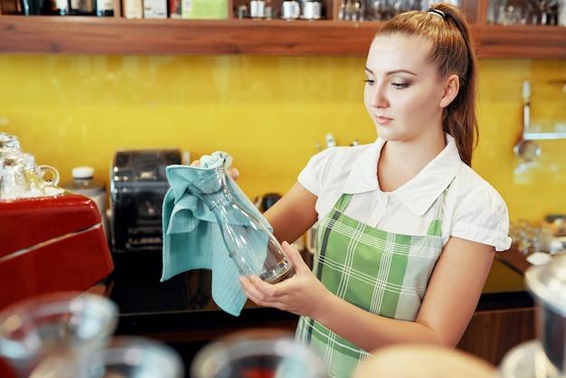 Junge barista frau, die glaswaren auswischt