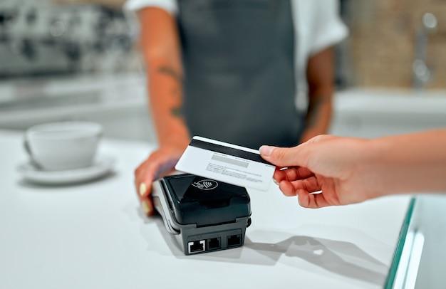 Junge barista-frau steht an der theke in einem café. der kunde bezahlt seine bestellung mit einer kreditkarte in einem café.