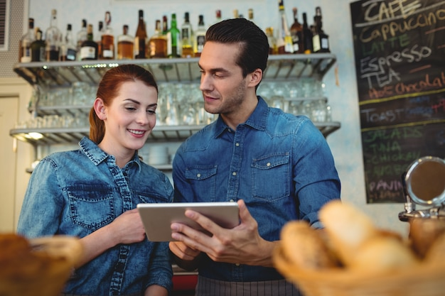 Junge baristas mit digitaler tablette am café