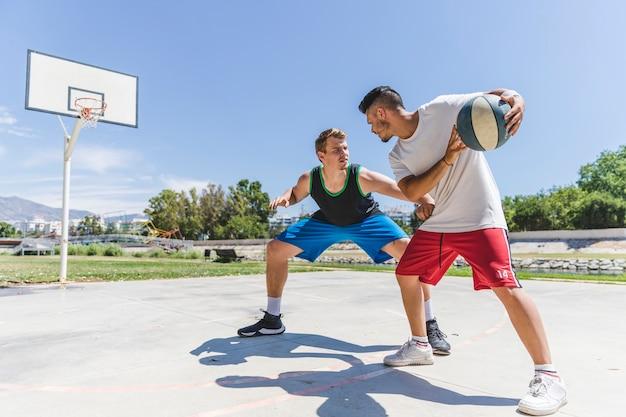 Junge basketball-spieler, die für ein spiel üben