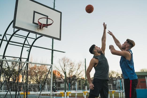 Junge basketballspieler, die am platz spielen