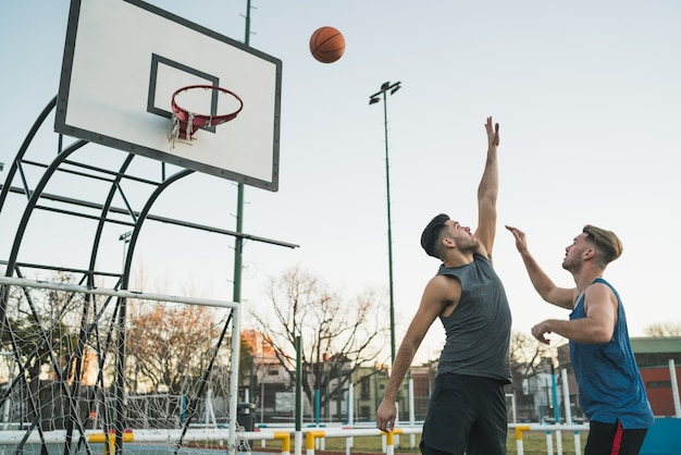 Junge basketballspieler, die eins zu eins auf dem außenplatz spielen. sport- und basketballkonzept.