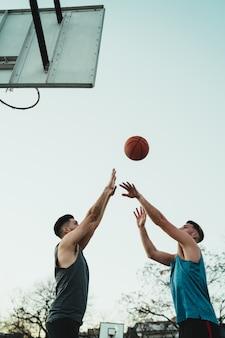 Junge basketballspieler, die eins zu eins spielen.