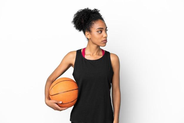 Junge basketballspielerin lateinische frau isoliert auf weißem hintergrund mit blick auf die seite