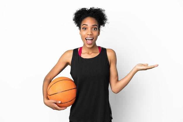 Junge basketballspielerin lateinische frau isoliert auf weißem hintergrund mit schockiertem gesichtsausdruck