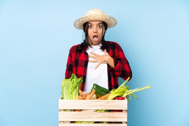 Junge bauernfrau, die frisches gemüse in einem hölzernen korb hält