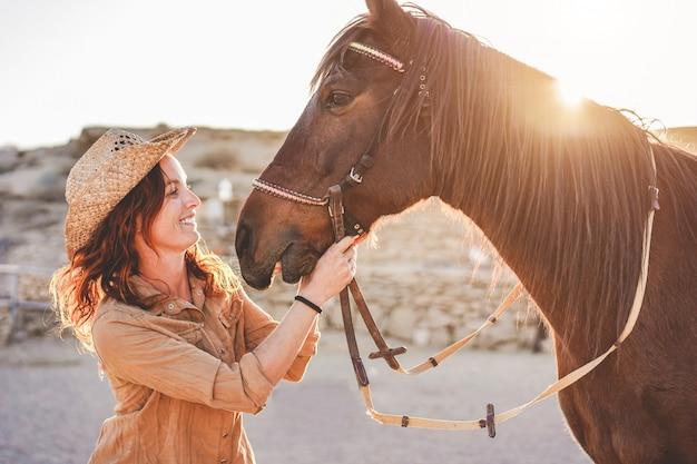 Junge bauernfrau, die mit ihrem bitlosen pferd an einem sonnigen tag innerhalb der corral-ranch spielt