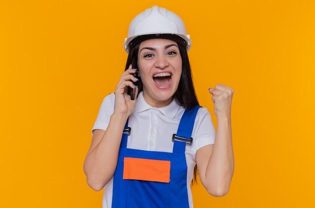 Junge baumeisterfrau in bauuniform und sicherheitshelm glücklich und aufgeregt geballte faust beim sprechen auf handy, das über orange wand steht