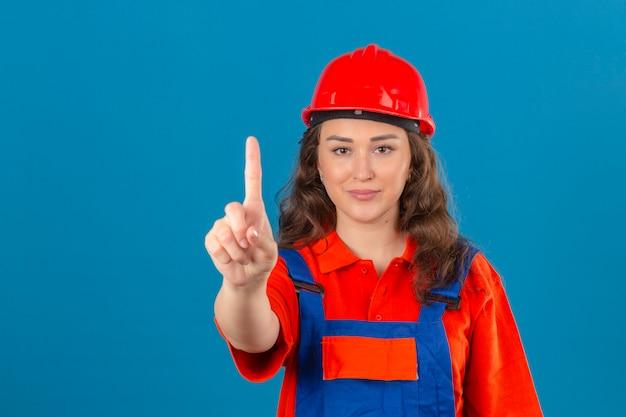 Junge baumeisterfrau in bauuniform und sicherheitshelm mit lächeln auf gesicht, das nummer eins mit zeigefinger über isolierter blauer wand zeigt