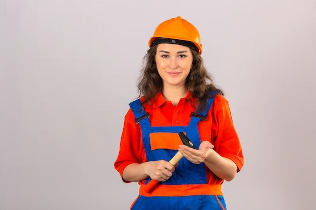 Junge baumeisterfrau in bauuniform und sicherheitshelm stehend mit hammer in den händen, die über isolierte weiße wand lächeln