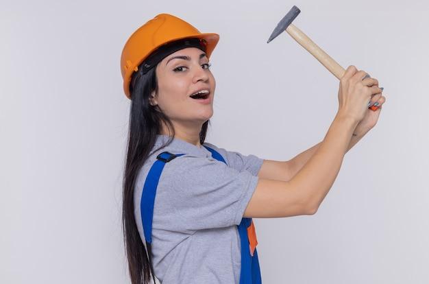 Junge baumeisterfrau in der bauuniform und im sicherheitshelm, der den hammer hält, der zuversichtlich weiß, die front steht über weißer wand