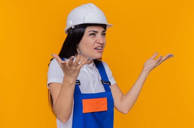 Junge baumeisterfrau in der bauuniform und im sicherheitshelm, die beiseite schauen, verwirrten sich ausbreitende arme zu den seiten, die unzufrieden sind, die über orange wand stehen