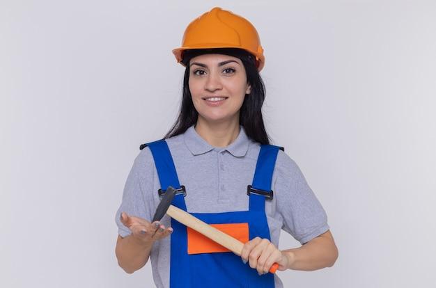 Junge baumeisterfrau in der bauuniform und im sicherheitshelm, die einen hammer schwingen, der vorne lächelnd zuversichtlich über weißer wand steht