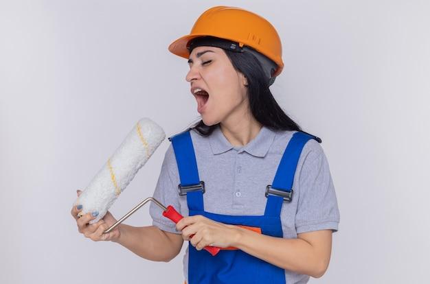 Junge baumeisterfrau in der bauuniform und im sicherheitshelm, die farbroller verwenden, der es als mikrofonsingen verwendet, das spaß hat, über weißer wand zu stehen