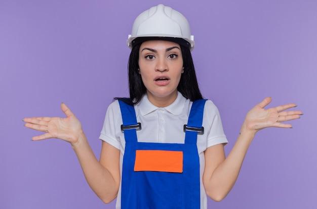 Junge baumeisterfrau in der bauuniform und im sicherheitshelm, die front betrachten, verwirrt mit erhobenen armen, die über lila wand stehen