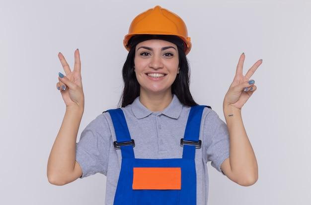 Junge baumeisterfrau in der bauuniform und im sicherheitshelm, die front glücklich und positiv lächelnd sehen, das v-zeichen zeigt, das über weißer wand steht