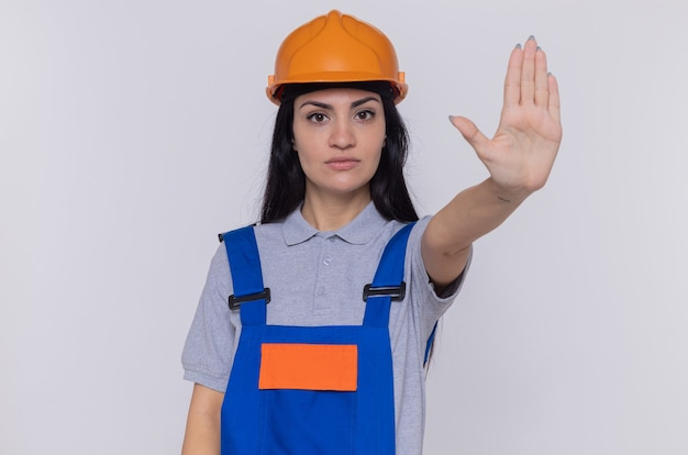 Junge baumeisterfrau in der bauuniform und im sicherheitshelm, die front mit ernstem gesicht betrachten, das stoppgeste mit hand steht, die über weißer wand steht