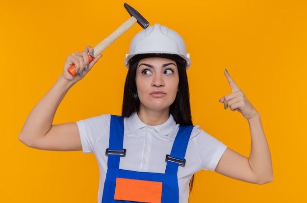 Junge baumeisterfrau in der bauuniform und im sicherheitshelm, die hammer über ihrem kopf halten, der zeigefinger lächelnd hat, der große idee hat, über orange wand zu stehen