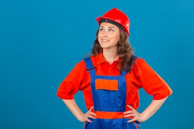 Junge baumeisterfrau in der bauuniform und im sicherheitshelm, die lächelndes glückliches gesicht über isolierter blauer wand suchen