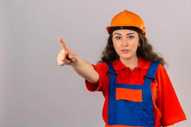 Junge baumeisterfrau in der bauuniform und im sicherheitshelm, die mit dem finger oben warnung vor gefahr über isolierter weißer wand stehen