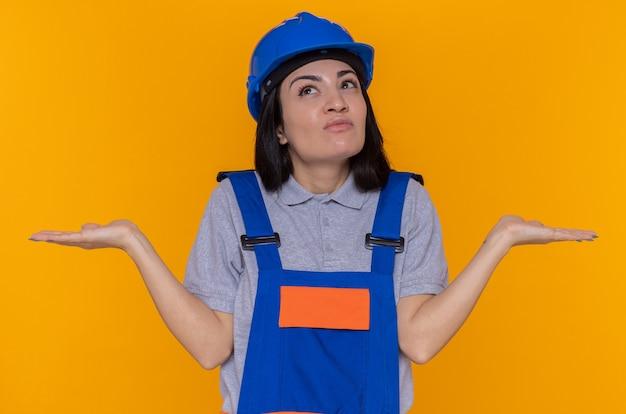 Junge baumeisterfrau in der bauuniform und im sicherheitshelm, die verwirrte achselzucken nach oben schauen, die keine antwort haben, die über orange wand steht