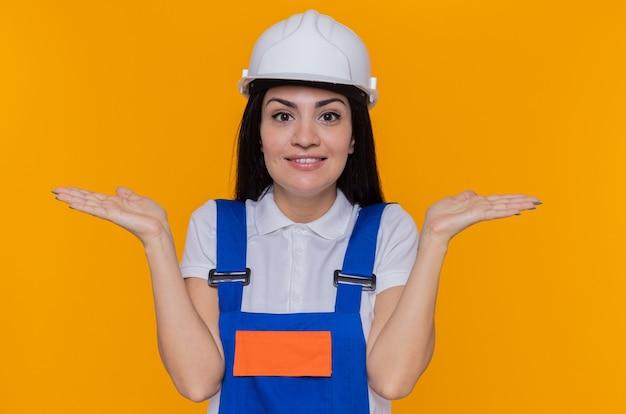 Junge baumeisterfrau in der bauuniform und im sicherheitshelm, die vorne lächelnd freudig ausbreitende arme zu den seiten betrachten, die über orange wand stehen