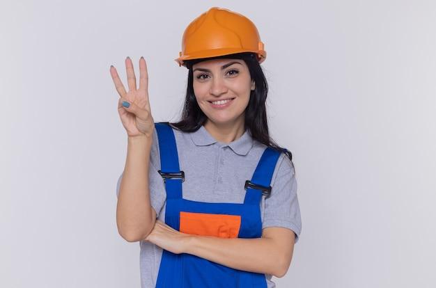 Junge baumeisterfrau in der bauuniform und im sicherheitshelm, die vorne lächelnd zeigt, zeigt nummer drei mit den fingern, die über weißer wand stehen