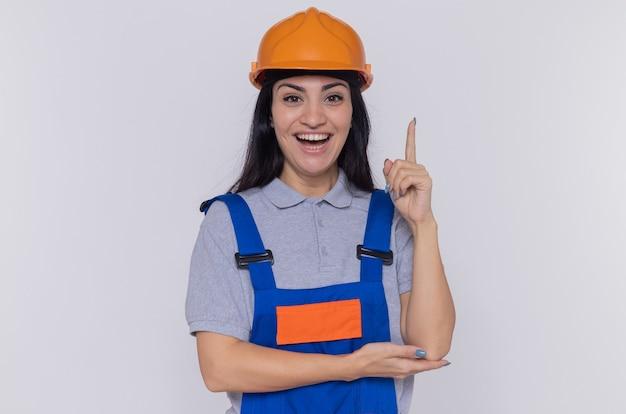 Junge baumeisterfrau in der bauuniform und im sicherheitshelm, die vorne mit dem lächeln auf intelligentem gesicht betrachten, das zeigefinger zeigt, der über weißer wand steht