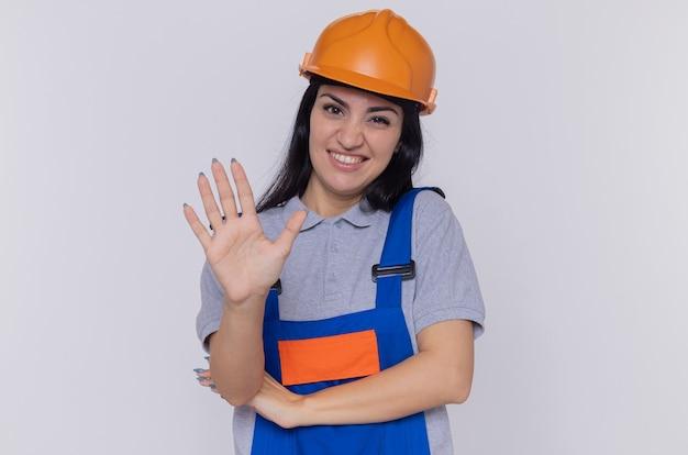 Junge baumeisterfrau in der bauuniform und im sicherheitshelm, die vorne mit skeptischem lächeln auf gesicht schauen, das offene handfläche zeigt, die über weißer wand steht