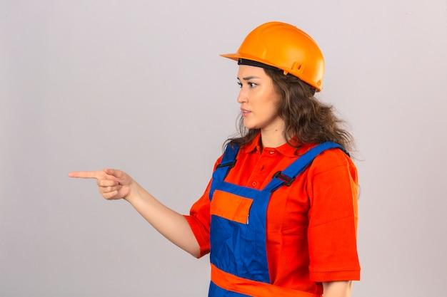 Junge baumeisterfrau in der bauuniform und im sicherheitshelm, die zur seite mit zeigefinger zeigen, der über isolierter weißer wand steht