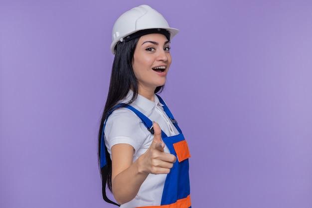 Junge baumeisterfrau in der bauuniform und im sicherheitshelm lächelnd, die freudig mit dem zeigefinger an der spitze stehend über lila wand zeigt