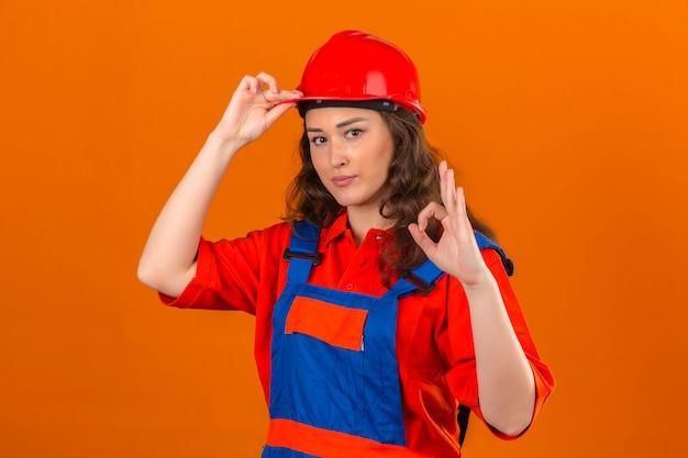Junge baumeisterfrau in der bauuniform und im sicherheitshelm mit dem lächeln, das helm berührt und ok zeichen über isolierte orange wand tut