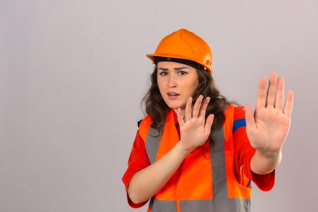 Junge baumeisterin in bauuniform und schutzhelm ängstlich und verängstigt mit angstausdruck stoppen geste mit händen über isolierte weiße wand