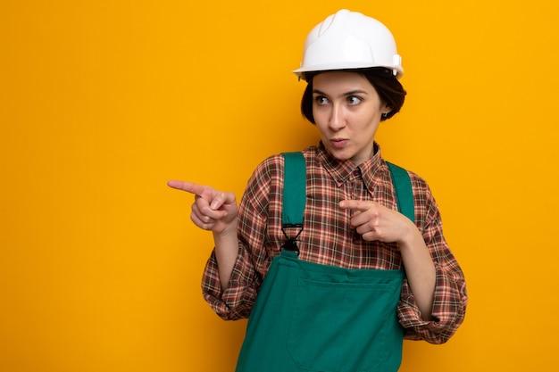 Junge baumeisterin in bauuniform und schutzhelm, die mit ernstem gesicht zur seite schaut, das mit den zeigefingern zur seite zeigt, die auf orange steht