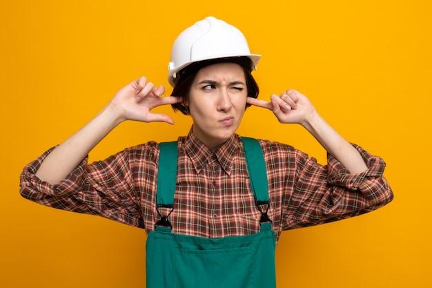 Junge baumeisterin in bauuniform und schutzhelm, die ohren mit fingern mit verärgertem ausdruck auf orange schließt