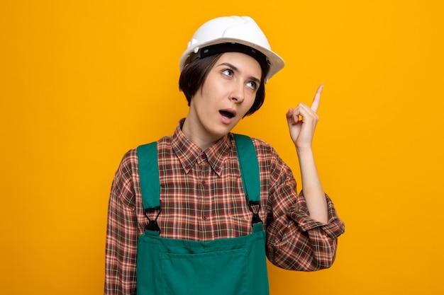 Junge baumeisterin in bauuniform und schutzhelm, die verwirrt nach oben schaut und zeigefinger auf orange steht