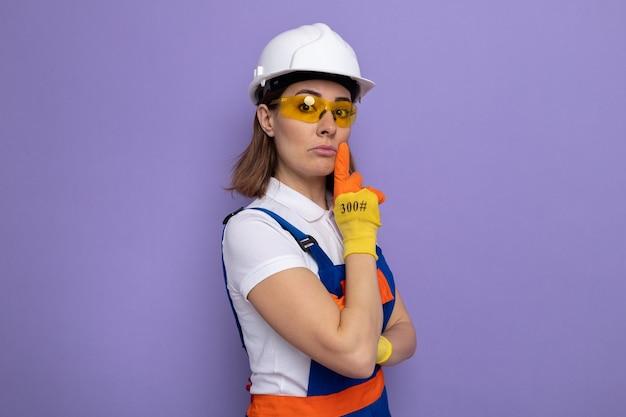 Junge baumeisterin in bauuniform und schutzhelm in gummihandschuhen mit gelber sicherheitsbrille, die mit ernstem, selbstbewusstem ausdruck aussieht