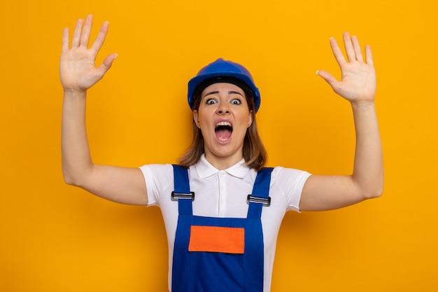 Junge baumeisterin in bauuniform und schutzhelm ist schockiert und hat angst, die arme in panik zu heben, die über orangefarbener wand stehen