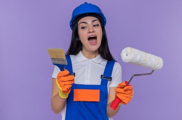 Junge baumeisterin in bauuniform und schutzhelm mit gummihandschuhen, die farbroller und pinsel halten und überrascht aussehen