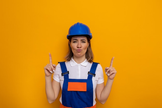 Junge baumeisterin in bauuniform und schutzhelm sieht verwirrt aus und zeigt große geste mit händen und fingern