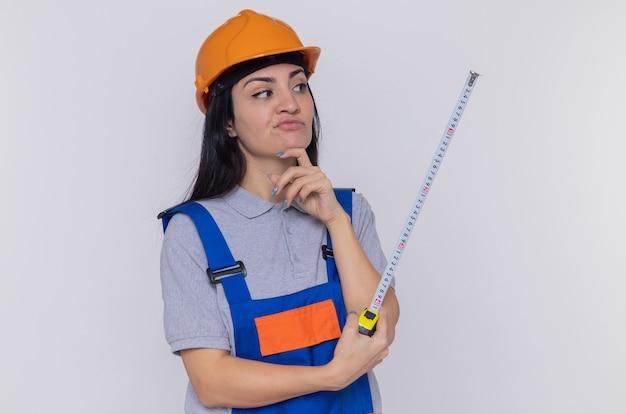 Junge baumeisterin in bauuniform und sicherheitshelm, die maßband hält, das es nachdenkliches ausdrucksdenken betrachtet, das über weißer wand steht