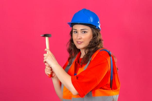 Junge baumeisterin in bauuniform und sicherheitshelm stehend mit hammer, der mit lächeln an der kamera über isolierter rosa wand schaut