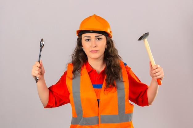 Junge baumeisterin in bauuniform und sicherheitshelm stehend mit schraubenschlüssel und hammer mit ernstem gesicht über isolierter weißer wand