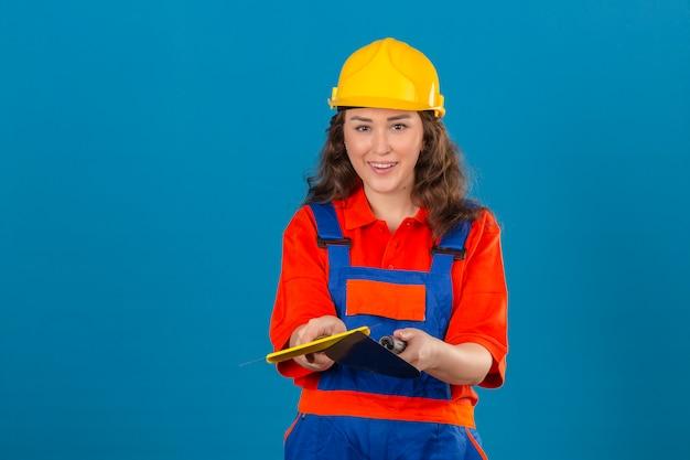 Junge baumeisterin in bauuniform und sicherheitshelm stehend mit spachtel lächelnd freundlich über isolierte blaue wand
